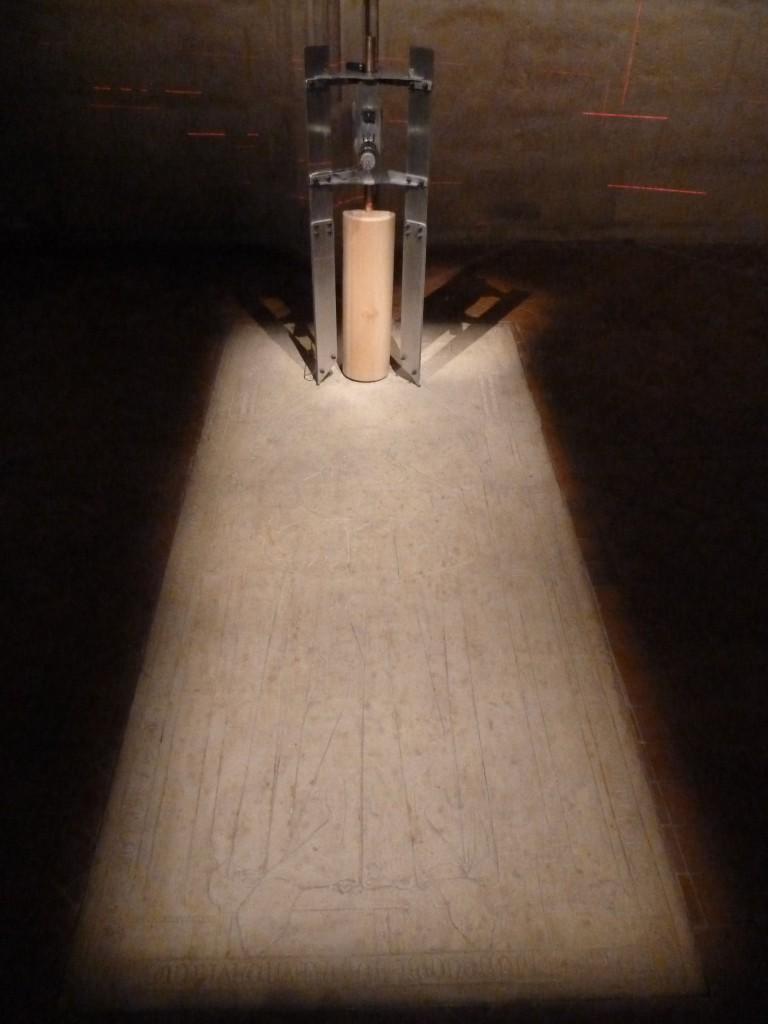 Alors ça c'est une machine qui fait retomber toutes les 60 secondes un cylindre en bois. Sur la tombe d'un moine que l'on voit au sol.